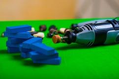Un trapano grigio con i piccoli pezzi di legno blu su un fondo verde Fotografia Stock Libera da Diritti