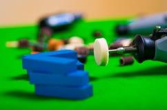 Un trapano grigio con i piccoli pezzi di legno blu su un fondo verde Immagine Stock Libera da Diritti