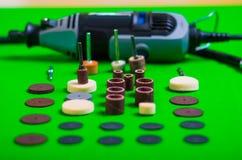 Un trapano grigio dietro degli accessori di perforazione su fondo verde Immagini Stock