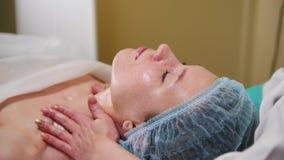 Un tratamiento del masaje de cara en clínica de la cosmetología El doctor mancha el aceite especial en la cara Masaje apacible almacen de video