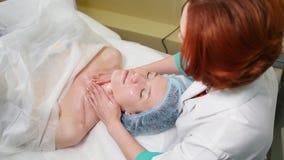 Un tratamiento del masaje de cara en clínica de la cosmetología El doctor mancha el aceite especial en la cara metrajes