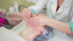 Un tratamiento del masaje de cara en clínica de la cosmetología Suavemente masaje de la barbilla almacen de metraje de vídeo