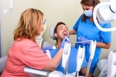 Un trattamento ottenente paziente in uno studio dentario Fotografia Stock