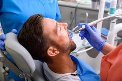 Un trattamento ottenente paziente in uno studio dentario Fotografia Stock Libera da Diritti