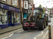 Un trattore agricolo resistente ad alta potenza sulla strada stretta attraverso un villaggio inglese Immagini Stock