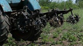Un trattore blu con un erpice metallico si spost indietroare nella fine dell'estate video d archivio