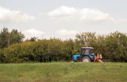 Un trattore che è usando per tagliare erba Fotografia Stock Libera da Diritti