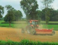 Un trattore che fertilizza un campo immagini stock