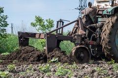Un trattore che funziona nel campo di trattamento in ambiente terrestre Fotografie Stock Libere da Diritti
