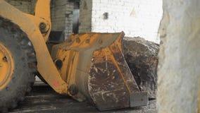 Un trattore con un secchio enorme nella parte anteriore spinge il ciottolo nell'uscita del capannone, movimenti grandi di una pie stock footage