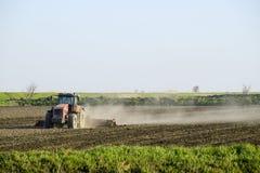 Un trattore con un aratro pone il suolo Coltivazione del suolo sul fie Fotografia Stock