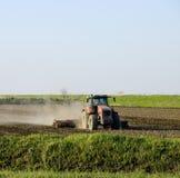 Un trattore con un aratro pone il suolo Coltivazione del suolo sul fie Fotografie Stock Libere da Diritti