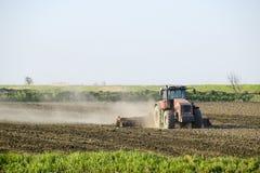 Un trattore con un aratro pone il suolo Coltivazione del suolo sul fie Immagine Stock