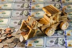 Un trattore del giocattolo rastrella un mazzo di centesimi di Stati Uniti contro un fondo di Immagine Stock