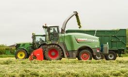 Un trattore di John Deere con il forager di Fendt Katana 65 Immagine Stock