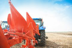 Un trattore moderno con un aratro trascinato sul campo un giorno soleggiato Immagine Stock