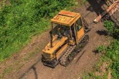 Un trattore porta gli alberi Raccolta degli alberi vecchi e cattivi Fotografie Stock