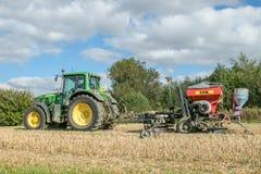 Un trattore verde con un seme perfora dentro un campo di stoppie Fotografie Stock Libere da Diritti