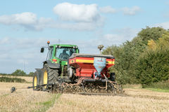 Un trattore verde con un seme perfora dentro un campo di stoppie Immagine Stock