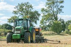 Un trattore verde con un seme perfora dentro un campo di stoppie Fotografia Stock