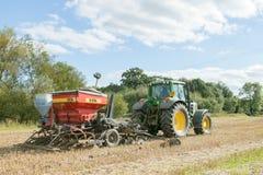 Un trattore verde con un seme perfora dentro un campo di stoppie Immagini Stock Libere da Diritti