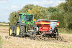 Un trattore verde con un seme perfora dentro un campo di stoppie Fotografia Stock Libera da Diritti