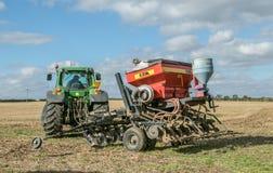 Un trattore verde con un seme perfora dentro un campo di stoppie Immagine Stock Libera da Diritti