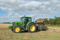 Un trattore verde con un seme perfora dentro un campo di stoppie Fotografie Stock