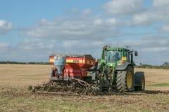 Un trattore verde con un seme perfora dentro un campo di stoppie Immagini Stock