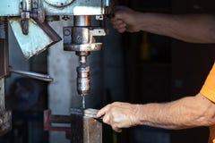 Un travailleur actionnant une machine industrielle de perceuse à l'intérieur d'une usine d'aluminiun photographie stock libre de droits