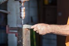 Un travailleur actionnant une machine industrielle de perceuse à l'intérieur d'une usine d'aluminiun photos libres de droits