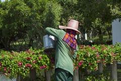 Un travailleur arrosant les fleurs Image stock
