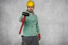 Un travailleur avec un grand marteau regarde l'appareil-photo Images stock