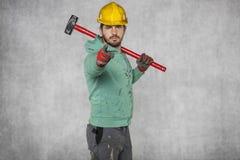 Un travailleur avec un grand marteau sur son épaule, points à vous Photos stock