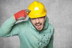 Un travailleur contrarié fou jetant un coup d'oeil dans un casque de protection photos libres de droits