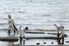 Un travailleur dans le biohazard adapte au boom de retenue d'huile usagée comme cleani Image libre de droits