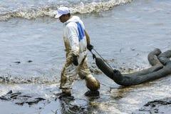 Un travailleur dans le biohazard adapte au boom de retenue d'huile usagée comme cleani Photos stock