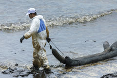 Un travailleur dans le biohazard adapte au boom de retenue d'huile usagée comme cleani Photo stock