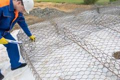 Un travailleur dans une salopette bleue fait le guide filaire pour une piscine naturelle image libre de droits