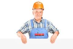 Un travailleur de la construction mâle retenant un panneau Photographie stock libre de droits