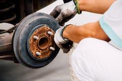 Un travailleur de mécanicien remplaçant le liquide des freins  Photo stock