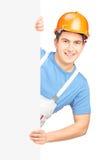 Un travailleur de sexe masculin avec le casque posant derrière un panneau vide Photographie stock libre de droits