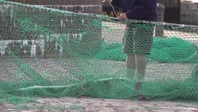 Un travailleur gauche fixe un extérieur en nylon vert de filet de pêche banque de vidéos