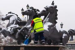 Un travailleur méconnaissable balaye la fontaine pendant quatre saisons Photos stock