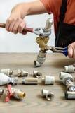 Un travailleur relie des éléments de la tuyauterie image stock