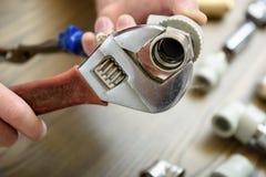 Un travailleur relie des éléments de la tuyauterie photographie stock