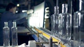 Un travailleur vérifie des bouteilles Le travailleur manuel féminin vérifie la nouvelle bouteille, alors qu'ils s'attaquent sur u banque de vidéos