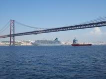 Un trazador de l?neas blanco y un buque de carga rojo debajo del puente del 25 de abril en Lisboa, Portugal, Europa imagen de archivo libre de regalías