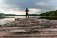 Un trekker solo en un embarcadero en el lago Saimaa en el Kolovesi N imagenes de archivo