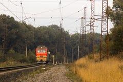 Un tren eléctrico rojo sin el material rodante se va a lo largo del carril imágenes de archivo libres de regalías